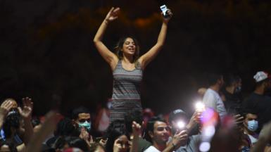 People celebrate in the streets of Tunis after Tunisian President Kais Saied announced the suspension of parliament