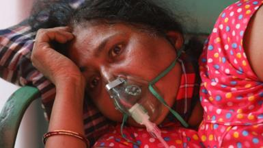 A woman breathing with the help of an oxygen cylinder in Delhi in April