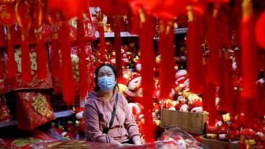 A vendor wearing a face mask following the coronavirus disease (COVID-19) outbreak waits for customers at a market selling Spring Festival ornaments ahead of the Chinese Lunar New Year festivity, in Beijing, China January 27, 2021