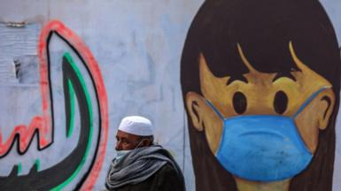 Palestinian man walking past mural in Gaza Strip.