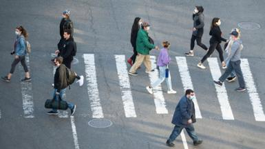 people in masks crossing road
