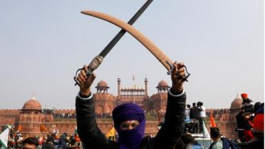 A farmer holds a sword during a protest against farm laws introduced by the government, at the historic Red Fort in Delhi, India, January 26, 2021