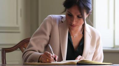 Archive image of the Duchess of Sussex signing a visitors book at Edes House, Chichester