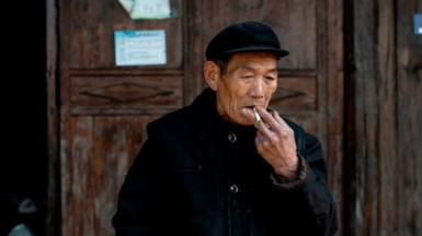Male Chinese farmer smoking a cigarette
