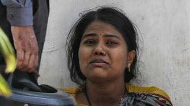 A woman crying outside a crematorium