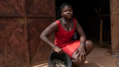 Alciony Fernandez, 14 years old, poses with her four kilos of cashews from her family farm she says she sells at 350 CFA per kilogram at a small store outside the capital, Bissau, has a scale that local cashew producers can use to weigh their crop. She walked about thirty minutes to the store to weigh the cashews.