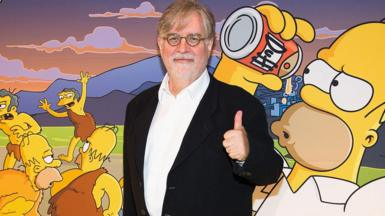 Matt Groening stands in front of a picture of Homer Simpson