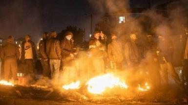 Armed community members gather around a fire to keep warm at a road block set up in Phoenix Township, North Durban, on July 15, 2021 to prevent looters from reaching the community.