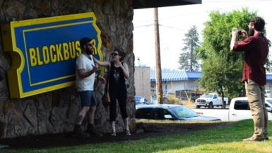 Tourists take pictures in front of Blockbuster sign