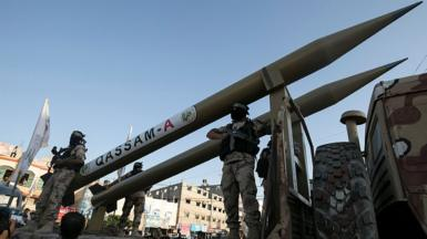 Palestinian militants from Hamas's military wing, the Izzedine al-Qassam Brigades, display a Qassam rocket at a parade in Rafah, southern Gaza, on 21 August 2016