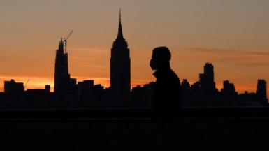 A person wearing a mask walks along the Hudson River as the sun rises behind the Empire State Building in New York City on May 14, 2020 as seen from Hoboken, NJ.