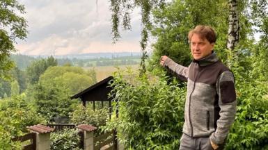 Milan Starec points towards the Turow power plant over the border