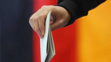 Hand holding ballot paper next to Germany flag