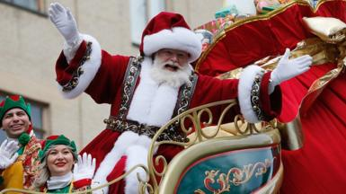 Santa Claus waves from his flotat during the annual Macy's Thanksgiving Day Parade in New York City, November 28, 2019
