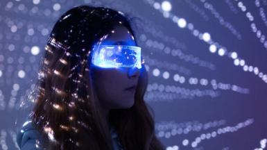 A woman wears augmented reality glasses in a dark room with white dotted lights in the background