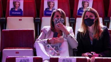Supporters sit next to posters of Ile-de-France region's president and candidate for reelection Valery Pecresse during a campaign meeting at the Cirque d'Hiver in Paris on June 24, 2021,