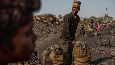 A man is filling bags with coal at the Jharia Coal mines