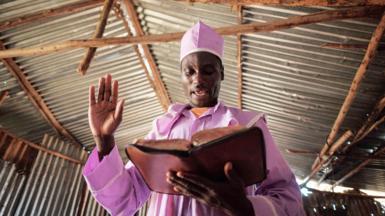 A worshipper of Adundo Messiah church reads the Bible during the Sunday church service in Kisumu, Kenya