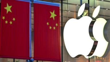 Apple logo on the front of a store in front of a nearby Chinese flag