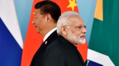 Chinese President Xi Jinping (L) and Indian Prime Minister Narendra Modi attend the group photo session during the BRICS Summit at the Xiamen International Conference and Exhibition Center in Xiamen, southeastern China's Fujian Province on September 4, 2017