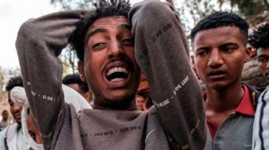 A man reacts as people gather around the body of a young man that witnesses say was shot by security forces after breaking curfew, capital of Tigray on February 27, 2021.