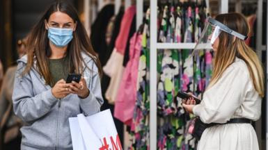 A woman wearing a mask walks out of a clothes shop