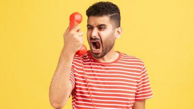 Angry nervous bearded man in striped t-shirt screaming and yelling talking retro landline phone, complaining on connection quality.