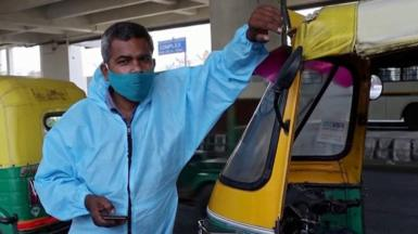 "Raj Kumar next to his ""tuk-tuk ambulance"""