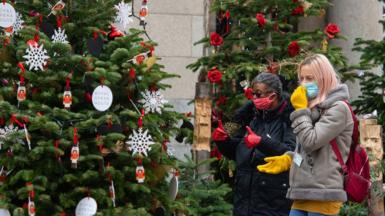 Women in face masks looking at Christmas trees