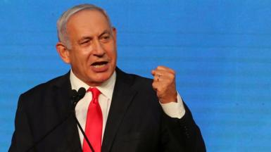 Benjamin Netanyahu gestures as he delivers a speech to supporters following the announcement of exit polls in Israel's general election in Jerusalem (24 March 2021)