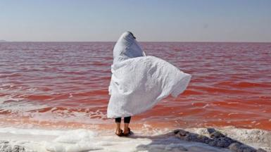 Person in a white shawl stands of the shoreline of Lake Urmia and its red-coloured water