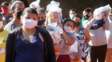 People carry plastic bags with food aid distributed at a favela in Sao Paulo