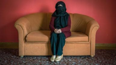 Sana sits defiant on the sofa of her temporary accommodation in Greece.