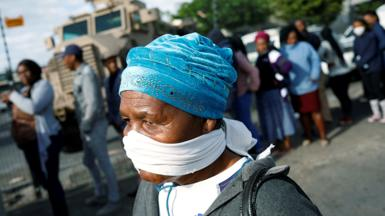An elderly woman covers her face with a makeshift mask as people queue to collect social grants and shop during a 21 day nationwide lockdown aimed at limiting the spread of coronavirus disease (COVID-19) in Khayelitsha township near Cape Town