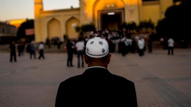 This picture taken on June 26, 2017 shows a Muslim man arriving at the Id Kah Mosque for the morning prayer on Eid al-Fitr in the old town of Kashgar in China's Xinjiang Uighur Autonomous Region.