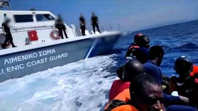 A migrant boat next to a Greek Coastguard boat