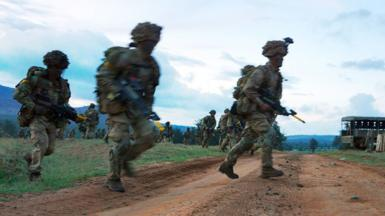 Soldiers run across a road during a simulated military exercise of the British Army Training Unit in Kenya (BATUK) together with the Kenya Defence Forces (KDF) March 26, 2018.