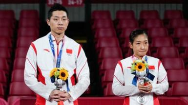 Silver medalists Xu Xin and Liu Shiwen of China pose on the podium after the Mixed Doubles Gold Medal Match against Jun Mizutani and Mima Ito of Japan.
