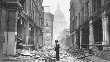 A postman attempting to deliver letters in a bomb-damaged street near Paul's Cathedral at the end of the London Blitz, May 1941