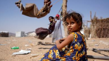 A girl sits as other children play on swings at a camp for internally displaced people in Marib, Yemen (16 February 2021)