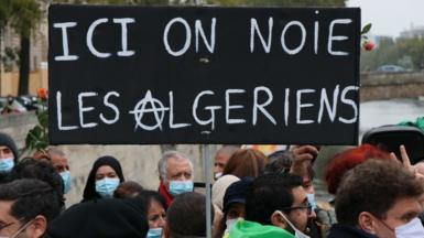 """Placard saying: """"Here we drown Algerians"""" seen at a remembrance ceremony to mark the 59th anniversary of the 1961 Paris massacre at the Pont Saint-Michel bridge over the River Seine in Paris, France - 17 October 2020"""