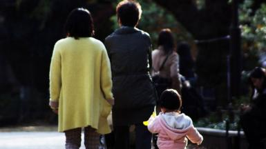 This picture taken on December 12, 2015 shows a family strolling at a park in Tokyo.