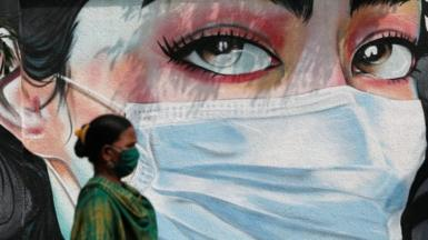 A woman walks past a graffiti of a girl wearing a protective mask amidst the spread of the coronavirus disease (COVID-19) in Mumbai, India, October 23, 2020.