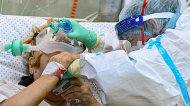 """A Covid-19 patient is helped to drink water inside the intensive care unit of the """"Pneumophysiology Institute Prof Dr Marius Nasta"""" in Bucharest, on October 7, 2021"""