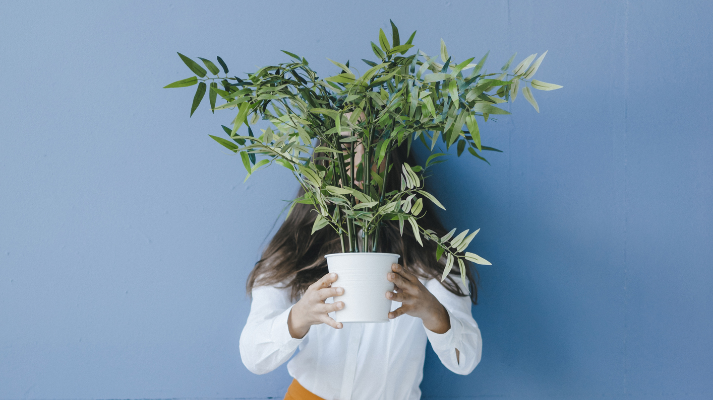 A woman holding a plant in front of her face