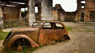 A rusting car sits on front of ruined buildings