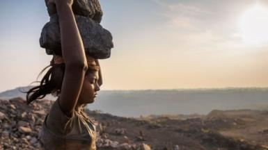 A woman carries coal on her head while working in the Jharia coal field in Jharkhand
