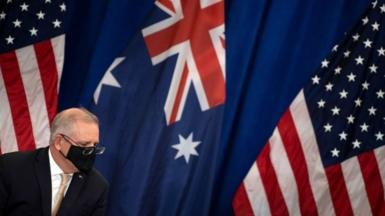 A masked Scott Morrison in front of the Australian and American flags
