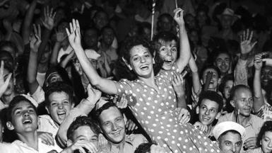 A crowd celebrates and holds a woman in the air