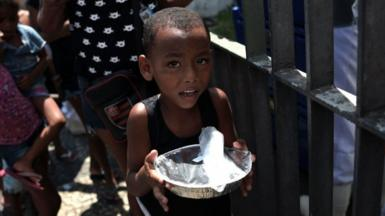 Boy receiving food handout in Rio de Janeiro, March 2021